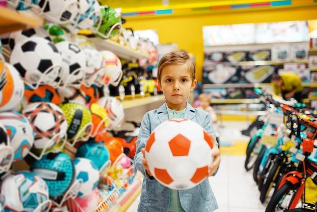 Mały chłopiec z piłką w sklepie dla dzieci, widok z przodu.