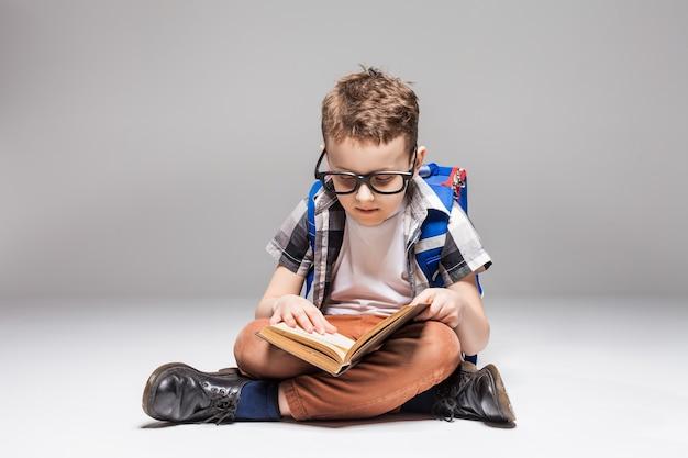 Mały chłopiec z plecakiem, czytając książkę w pozie jogi