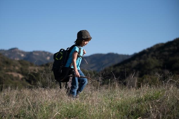 Mały chłopiec z plecakiem na wędrówki po malowniczych górach. chłopiec lokalny turysta wybiera się na lokalną wędrówkę