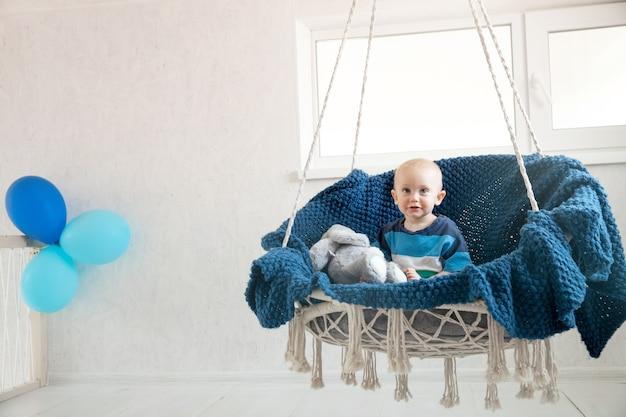 Mały chłopiec z pluszową zabawką siedzi na wiszącym krześle wśród balonów. to są pierwsze urodziny