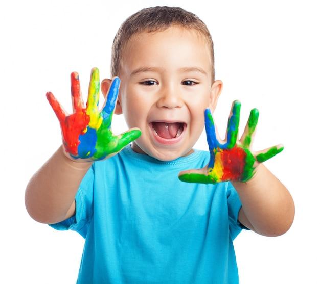 Mały chłopiec z rękami pełnymi farby, z otwartymi ustami