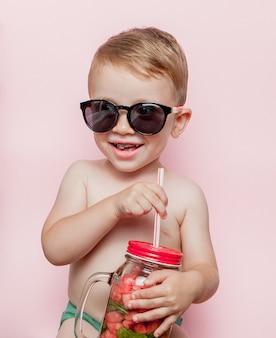 Mały chłopiec z słoikiem zimnej świeżej lemoniady z kawałkiem arbuza i lodem na różowo.