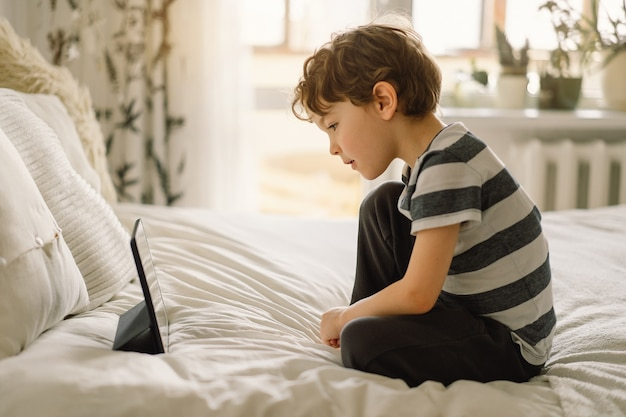 Mały chłopiec z tabletem w pokoju. chłopiec grać w grę na tablecie. dziecko z gadżetem