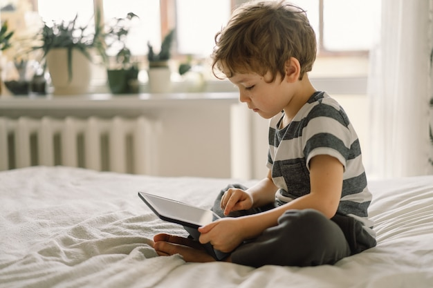 Mały chłopiec z tabletem w pokoju