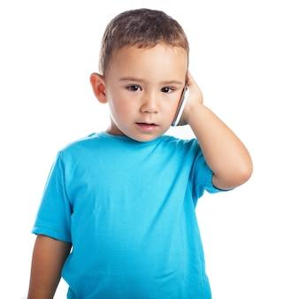 Mały chłopiec z telefonem w uchu