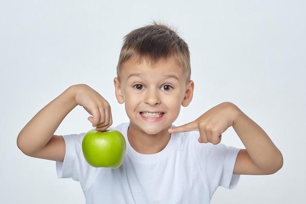 Mały chłopiec z uśmiechem trzyma zielone jabłko i wskazuje na nie palcem.