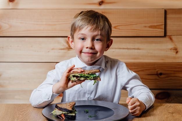 Mały chłopiec z wegetariańskie kanapki z chlebem pełnoziarnistym