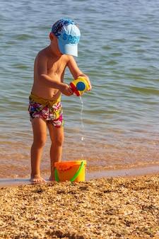 Mały chłopiec z wiaderkiem i konewką bawi się na piaszczystej plaży w letni dzień