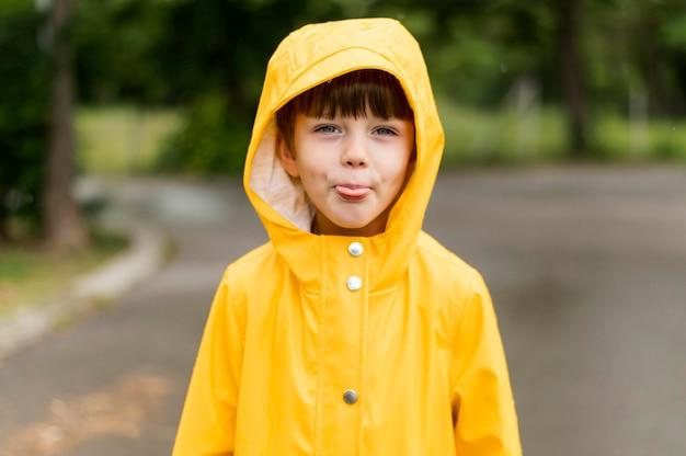 Mały chłopiec z wystawionym językiem w płaszczu przeciwdeszczowym