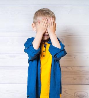 Mały chłopiec z zamkniętymi oczami rękami