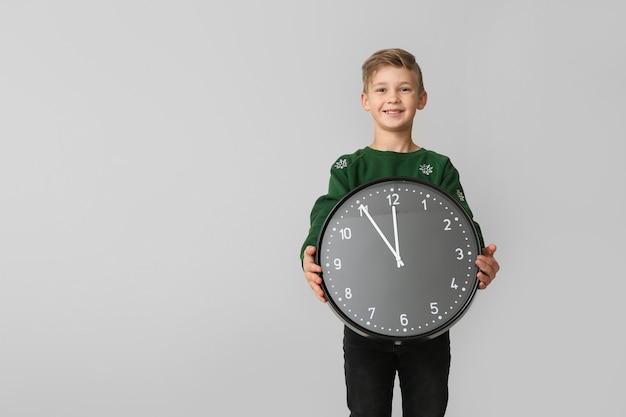 Mały chłopiec z zegarem na lekkiej powierzchni. koncepcja odliczania bożego narodzenia