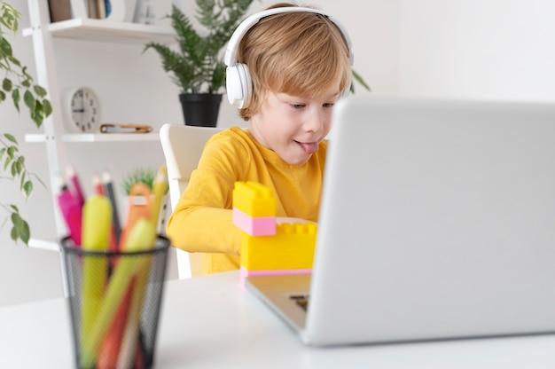 Mały chłopiec za pomocą laptopa i słuchawek w domu