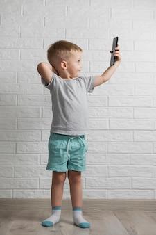 Mały chłopiec za pomocą makiety telefonu