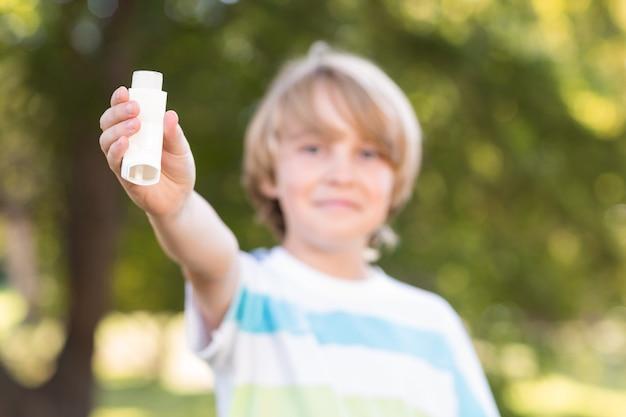 Mały chłopiec za pomocą swojego inhalatora