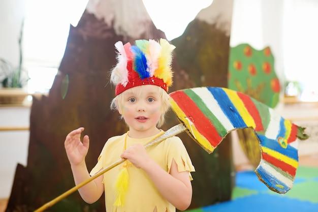 Mały chłopiec zaangażowany w performance teatru dziecięcego studio w roli indian amerykańskich.