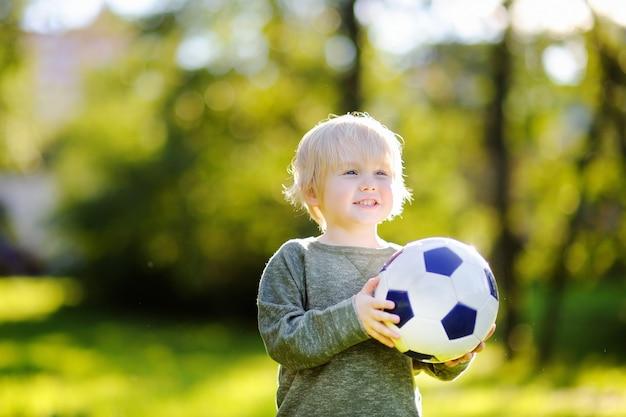 Mały chłopiec zabawy gra w piłkę nożną w słoneczny letni dzień