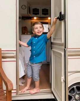 Mały chłopiec zaglądający za drzwi swojej przyczepy kempingowej