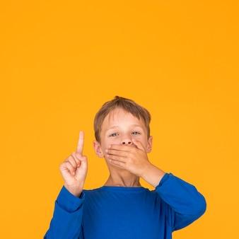 Mały chłopiec zakrywa usta i wskazuje