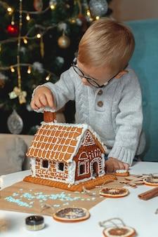 Mały chłopiec zdobi świąteczny domek z piernika