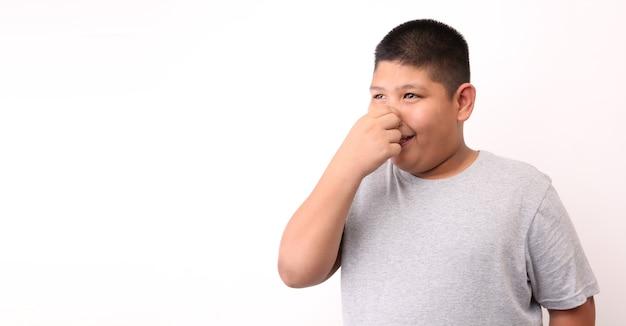 Mały chłopiec źle pachnie na białym tle.