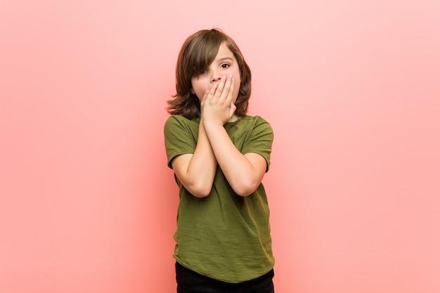 Mały chłopiec zszokowany, obejmujące usta rękami.