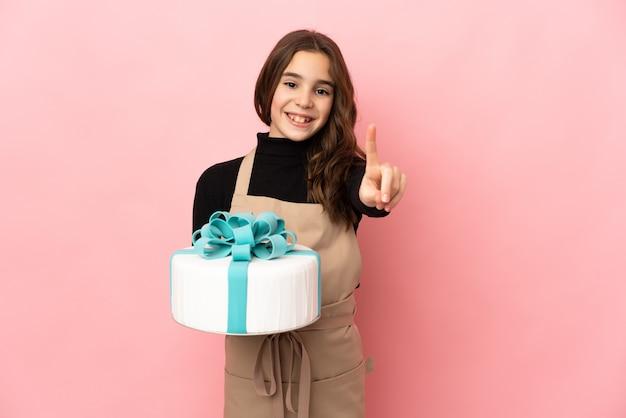 Mały cukiernik trzyma duży tort na białym tle na różowej ścianie, pokazując i podnosząc palec