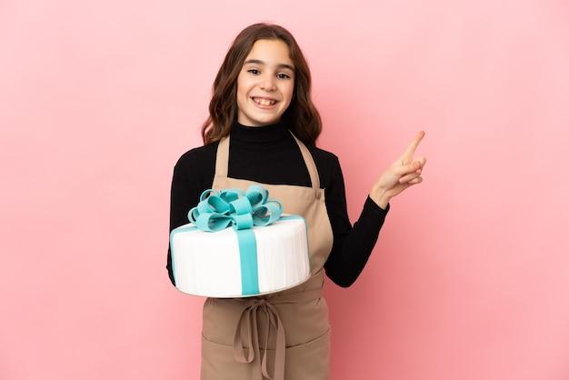 Mały cukiernik trzymając duży tort na różowej ścianie wskazując w bok, aby przedstawić produkt