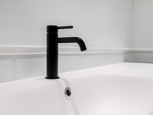 Mały czarny kran i umywalka w białej, czystej przestrzeni w łazience