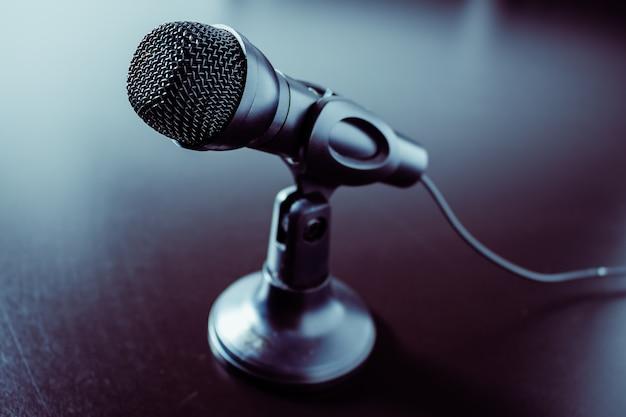 Mały czarny mikrofon biurkowy z przewodem i niską podstawką na czarnym stole. nowoczesny styl, koncepcja komunikacji i mowy.