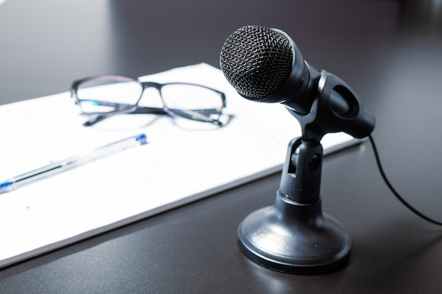 Mały czarny mikrofon biurkowy z przewodem i niskim stojakiem na czarnym stole obok notatnika, okularów i okularów