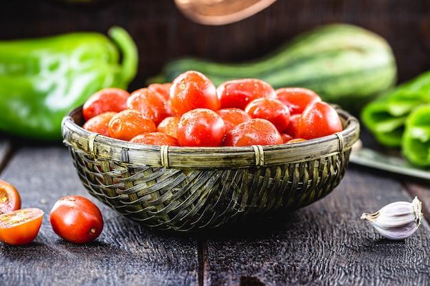 Mały czerwony pomidor, świeże warzywo używane w kuchni brazylijskiej. ciemny słomkowy kosz z żywnością ekologiczną