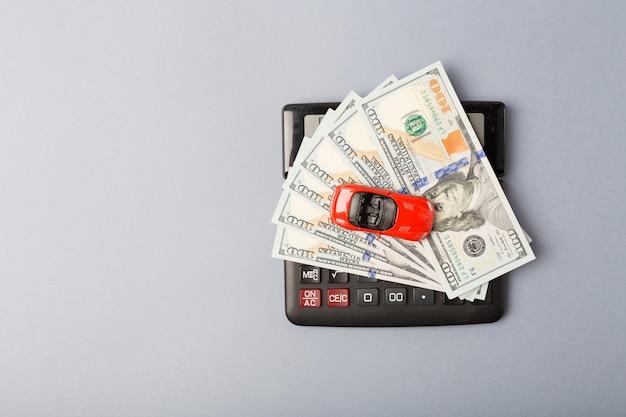 Mały czerwony samochód na kalkulatorze i stos dolarów pieniędzy. koncepcja kredytu samochodowego. wynajem samochodu. oszczędności. wolna przestrzeń. skopiuj miejsce.