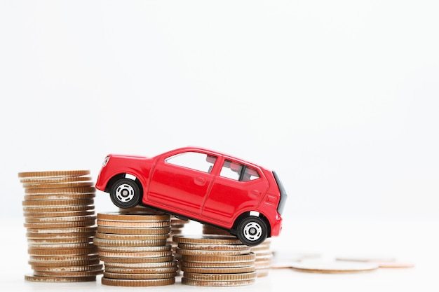 Mały czerwony samochód nad wieloma monetami ułożonymi w stosy. na finansowanie kosztów kredytów bankowych. ubezpieczenie, kupowanie koncepcji finansowania samochodu. kup i zapłać w ratach zaliczkę na samochód.