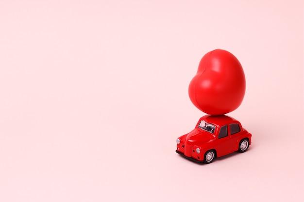 Mały czerwony samochodzik retro z sercem na dachu na różowej koncepcji dostawy prezentów walentynki