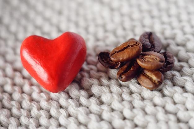 Mały czerwony serce na trykotowym tle obok kawowych adra