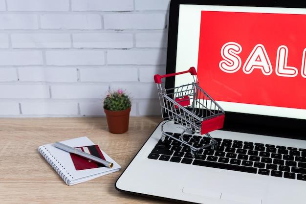 Mały czerwony wózek na zakupy lub tramwaj na laptop klawiaturze, technologia zakupy biznesowy online pojęcie