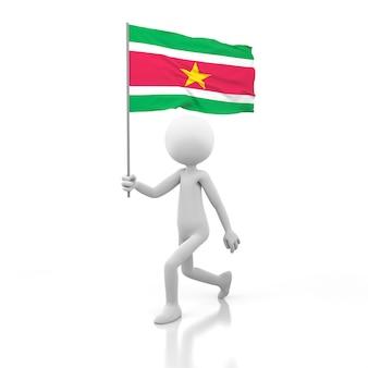 Mały człowiek chodzący z flagą surinamu w dłoni. obraz renderowania 3d