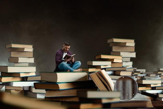 Mały człowiek czytający wśród dużych książek i podręczników, efekt skali. zdobywanie wiedzy i koncepcji edukacji. student studiujący przedmiot przed egzaminem