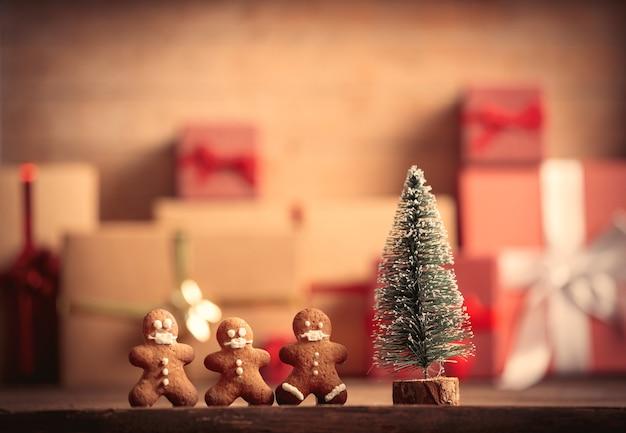 Mały człowiek z piernika i choinka na stole z prezentami na tle