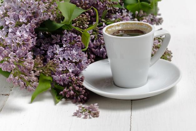 Mały delikatny elegancki bukiet wiosennych kwiatów i filiżanka na białym drewnianym stole, poranne śniadanie