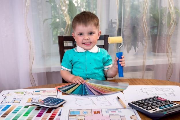 Mały, designerski chłopiec z próbnikiem koloru i wałkiem