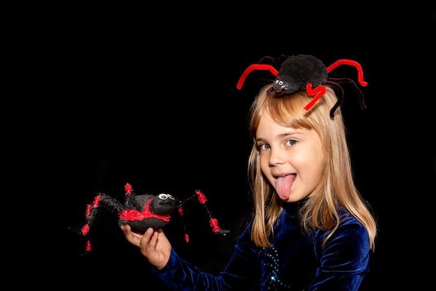 Mały diabełek z wielkim pająkiem na głowie iw dłoniach