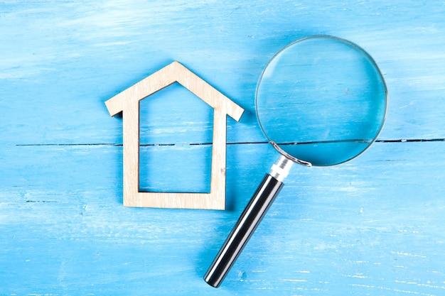 Mały dom i szkło powiększające na niebieskim drewnianym stole. koncepcja wyszukiwania