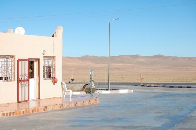 Mały dom przy drodze w kierunku pustyni z jasnym błękitnym niebem