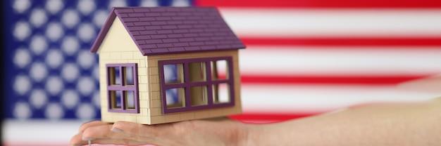Mały dom z kluczami pod ręką na tle amerykańskiej flagi