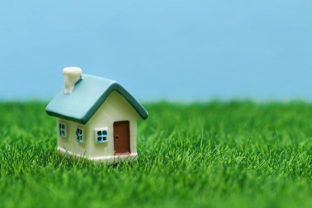 Mały dom zabawki na tle trawy i nieba.