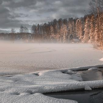 Mały domek na skraju lasu nad jeziorem zimą we mgle.