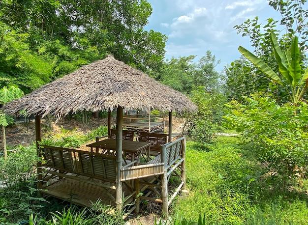 Mały domek z suchej trawy w zielonym ogrodzie