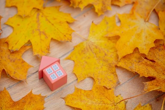 Mały domek zabawka obok jesiennych liści na stole