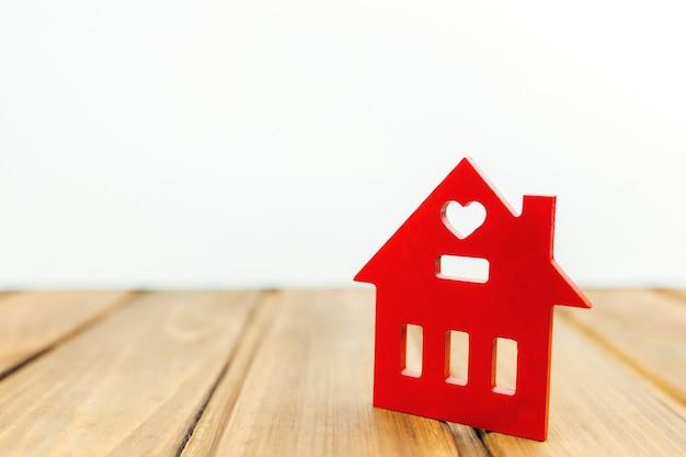 Mały drewniany czerwony domek na drewnianym stole